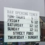 opening time sign using changeable letters in window of bar